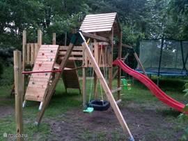 Uitgebreide speeltuin met klimwanden, schommels, glijbaan, rekstok, loopbrug, klimnet, trampoline, boomhut en kabelbaan