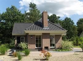 Terras en buitenhaard (voorzijde).In de bossen gelegen en volop mogelijkheden te genieten van de zonnige tuin rondom de woning met diverse terassen.