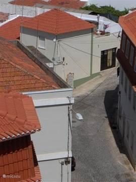 Uitzicht vanaf dakterras de straat in.