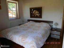Spacious master bedroom with double bed and large wardrobe.