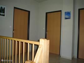 Overloop via trap te bereiken. Toegang tot de twee grote slaapkamers, een kleinere en de badkamer.