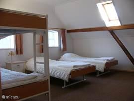 Slaapkamer 4 pers. met uitzicht op de boerderij en het natuurgebied de Leemputten.