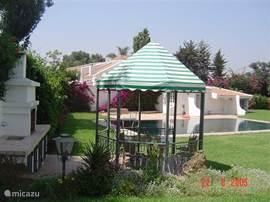 BBQ /zwembad, zit ruimte afgedekt van de zon met een glazen eettafel en stoelen. Heerlijk voor een lunch, ontbijt of BBQ