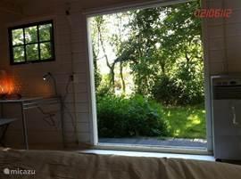 Uitzicht op de tuin vanuit slaapkamer 1 met openslaande deuren, net als slaapkamer 3.