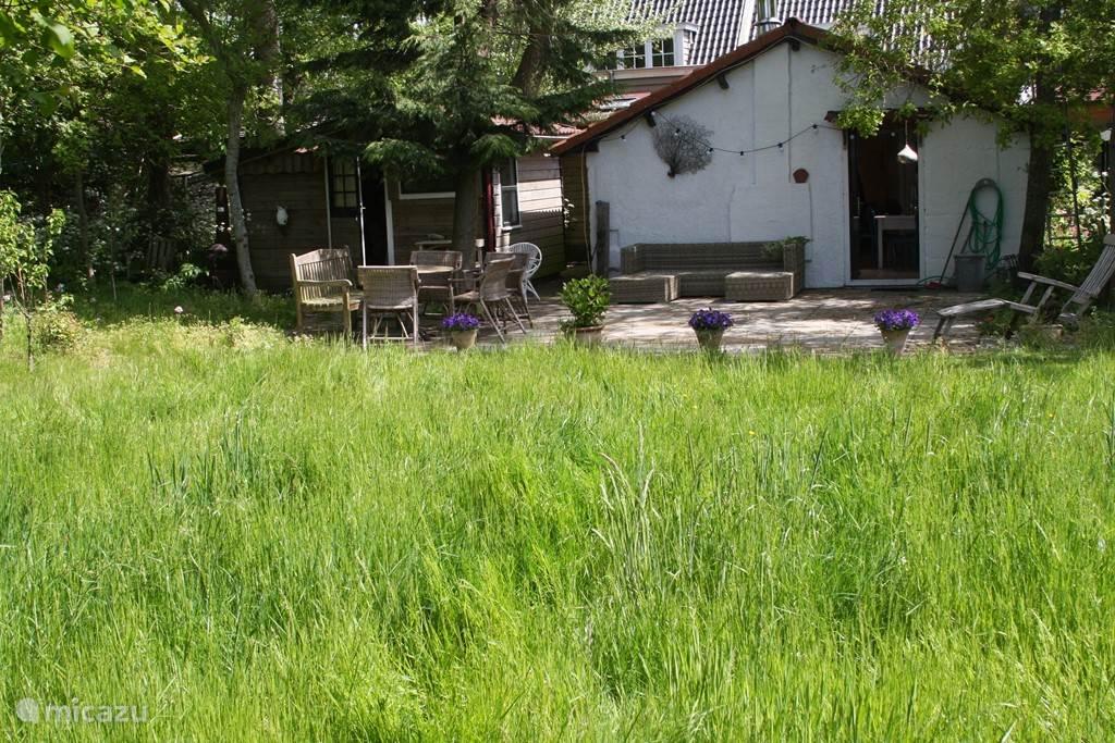 Tuin van 1100 m2 met 350 m2 grasveld (nu gemaaid).  Vooraanzicht hoofdgebouw, met links de losstaande schuur als 4e slaapkamer (niet spik&span) en daarachter de derde aangebouwde slaapkamer.