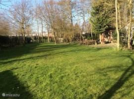 Het grasveld (350 mm2) behorend bij de tuin, met links slaapkamer 4 in het tuinhuis gelegen tegen het huis aan.