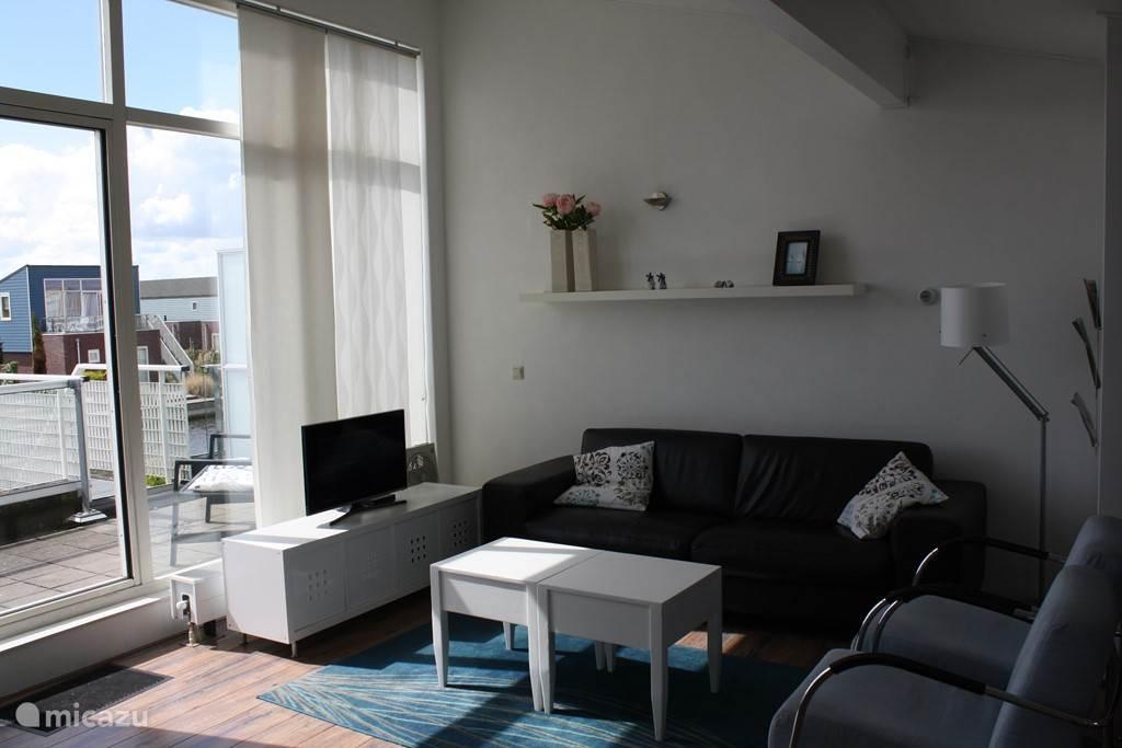 Zonnige living met schuifpui naar het dakterras. Vanaf het dakterras kunt u via de buitentrap naar het aan het water grenzende terras.