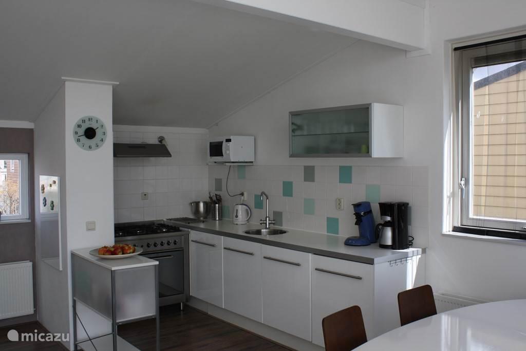 Keuken met div. apparatuur. O.a. een vaatwasser, magnetron en een vijfpits gasfornuis met wokbrander en oven.