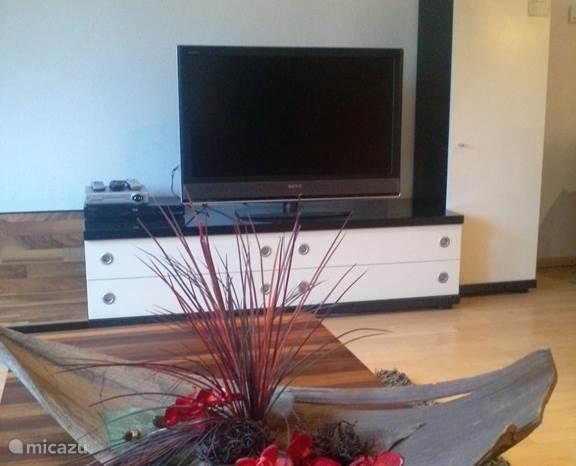 De woonkamer is modern ingericht en is voorzien van luxe meubels. Twee leren bankstellen en een salontafel.