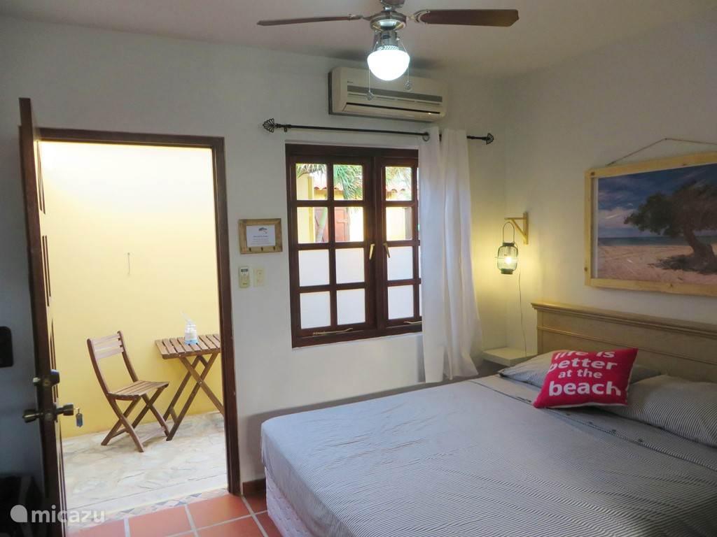 Aruba Studio B - Queen size bed en zitje bij de entree