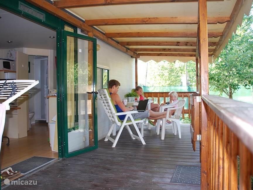 Op de ruime overdekte houten veranda kunt u heerlijk relaxen. Er staan 2 verstelbare stoelen met kussens, stapelstoelen en een tafel met bankje.