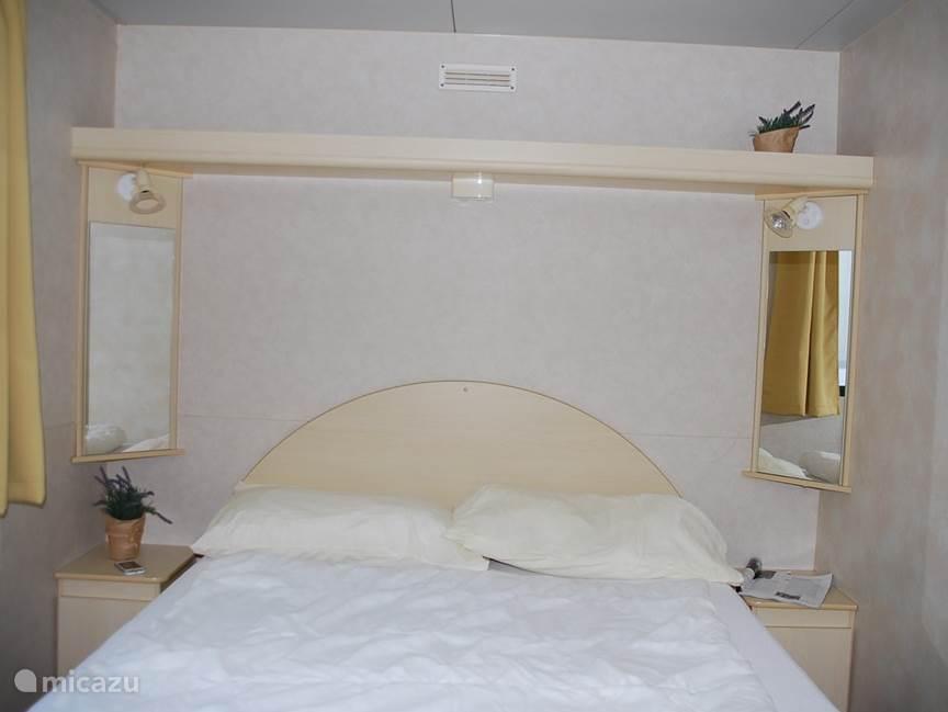 De ouderslaapkamer met een tweepersoonsbed. Op het bed ligt een tweepersoons matras, een molton, een tweepersoons dekbed en twee kussens met een sloop.