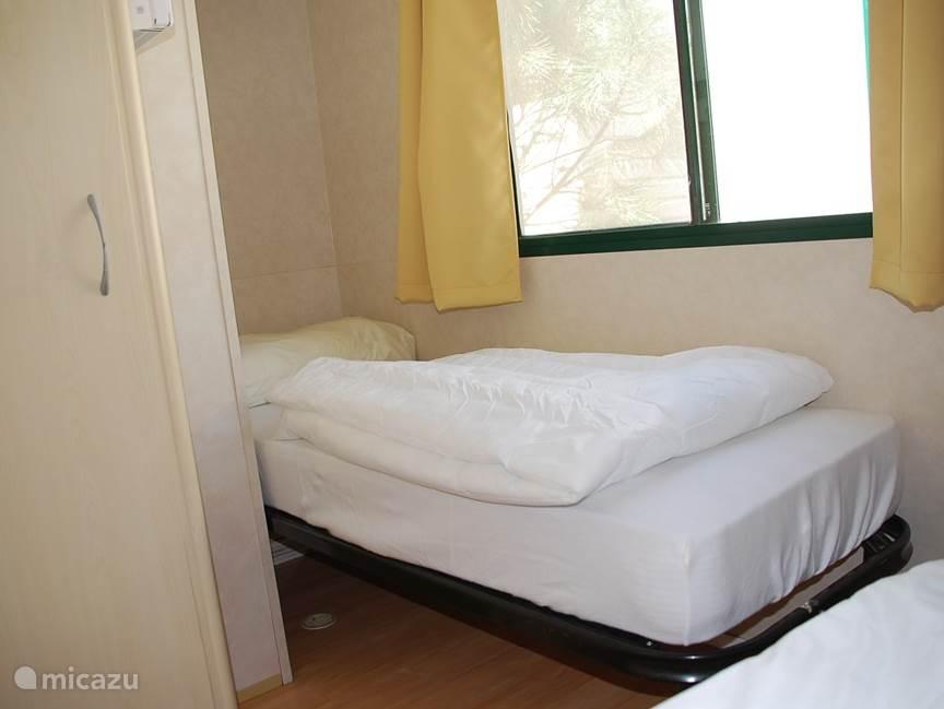Tweede slaapkamer met stapelbed en een eenpersoonsbed. Op de bedden ligt een molton, een dekbed en een kussen met sloop.