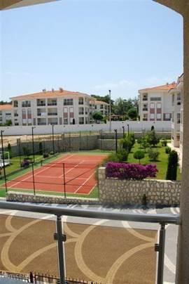 Uitzicht vanuit woonkamer op tennisbaan.
