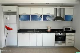 De keuken heeft een riante koel/vries combinatie. Verder is er een oven, magnetron en een wasmachine.