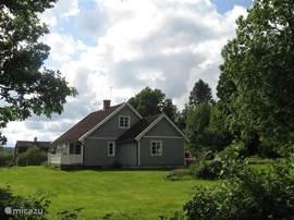 De voorzijde van de woning in de zomer