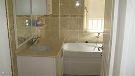 Badkamer Begane grond met wastafel, toilet, ligbad en aparte douchehoek. Handdoeken zijn aanwezig.