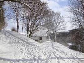 Huisje in de winter. Vanaf de bospad genomen