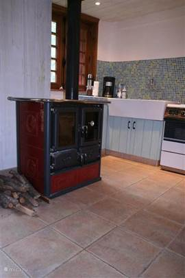 photo 2 kitchen with wood oven stove and sink in background
