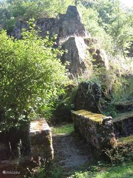 garden: bridge over the beef with rock in the background.