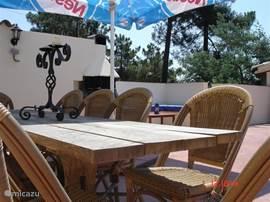 De eettafel met bbq en lounge bank. De barbeque kan ook als open haard worden gebruikt.(denk wel om de bosbranden!)