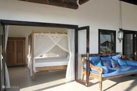 Eén van de vier slaapkamers met twee enkele bedden en op het terras het daybed.