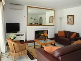 Gezellige woonkamer met een comfortabele 3 en 2 zits bank, losse rotan fauteuil en eethoek