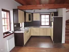 Keuken met twee openslaande ramen. Grote ijskast met vriesruimte.