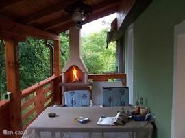 Het terras met een prachtig uitzicht. Zowel overdag tijdens uw ontbijt als ook 's avonds tijdens het grillen. Geen rook omdat de schoorsteen tot boven het dak uitloopt.