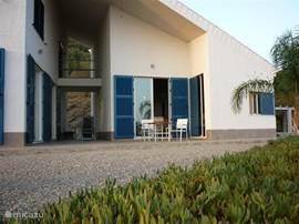 Het terras voor de woonkamer. De buitengang links is ook bij warm weer heerlijk koel.