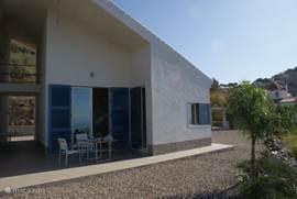 Terras voor het gastenverblijf.  Op het terrein zijn verschillende terrassen in de schaduw en in de zon op diverse niveaus.