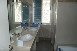 De grote, lichte badkamer is voorzien van dubbele wastafels, douche, bad en mooie verlichting. Het toilet is apart.