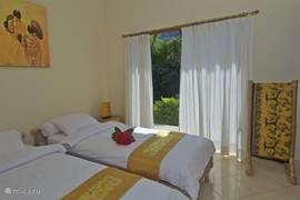 Slaapkamer met twee eenpersoons bedden airco en eigen badkamer.
