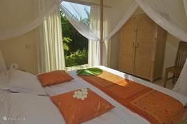 Slaapkamer met tweepersoonsbed met klamboe, sirco en eigen badkamer.