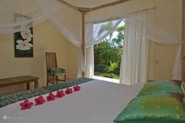 Nog een slaapkamer met hemelbed en openslaande deuren naar de tropische tuin. Natuurlijk met airco en eigen badkamer.