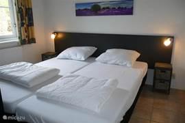 Slaapkamer beneden met twee boxsprings met dekbed, nachtkastjes en leeslampjes. Grote kledingkast in de slaapkamer. Plavuizen vloer.