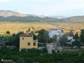 Uitzicht vanuit terras op het boerenhuis en de bergen.