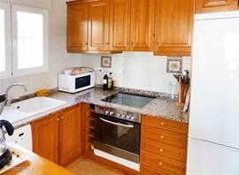 Keuken met grote koelkast, electrische fornuis en wasmachine. Alles is in prima staat.