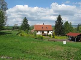Overzicht van huize Bara in het voorjaar met tuin, prieel, carport en terras. De tuin is afgezet met een hek behalve bij de oprit. Hierdoor is de tuin ook veilig voor kleine kinderen.  Onder de carport staat de zandbak en kunt u de hangmat ophangen!