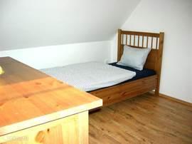 De 2e grote slaapkamer boven met 2 losse bedden en traphekje is ook erg ruim. Hier vindt u een ladekast.