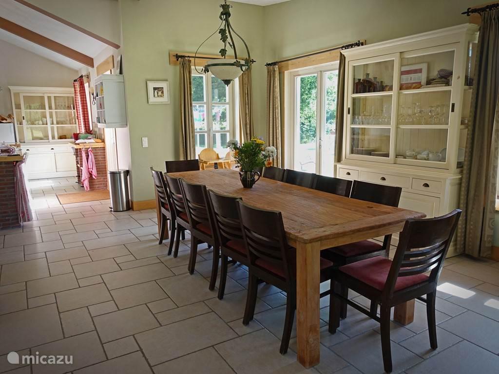 Eetkamer voor 12 personen, 2 kinderstoelen aanwezig. (gratis) Ruim uitgeruste keuken met electrische kookplaat, vaatwasser, combi magnetron.