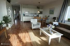 vanaf het balkon een zicht op de woonkamer + keuken met doorgang naar de twee slaapkamers