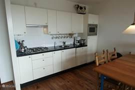 blik op de keuken met alle apparatuur: oven/magnetron, ijskast, afwasmachine etc
