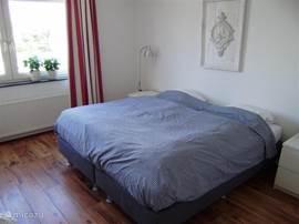ouderslaapkamer met twee eenpersoonsbedden tegen elkaar, grote hang/legkast, TV.