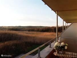 balkon van de Duinerei met een prachtig zicht op de duinen, 's avonds laat nog de zon op het terras.