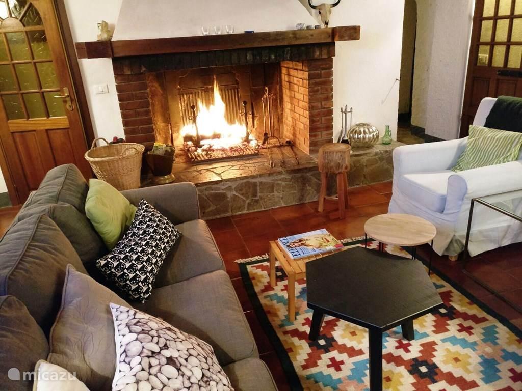 Woonkamer/living van Casa al Pino met open haard. Het huis heeft 2 zithoeken, eentje bij de open haard en satelliet tv en een ernaast met een hoekbank, om een boek te lezen of voor de kinderen.....