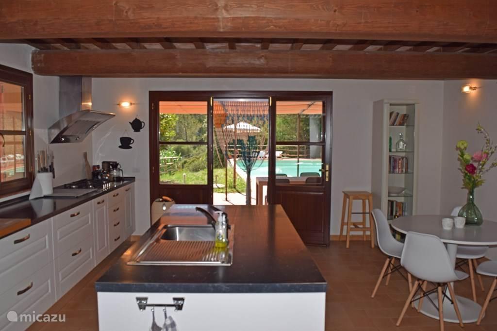 Casa al Pino heeft een compleet ingerichte keuken met eiland, kleinere eettafel voor een ontbijt en openslaande deuren naar terras en zwembad.