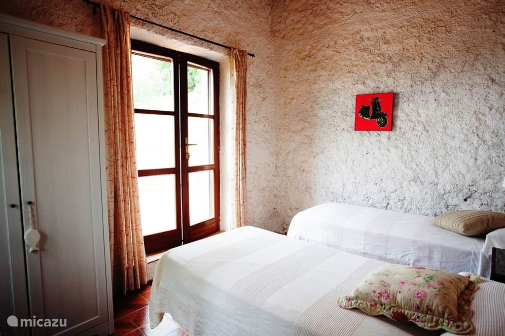 Slaapkamer met 2 eenpersoonsbedden en deur naar balkon/ terras.