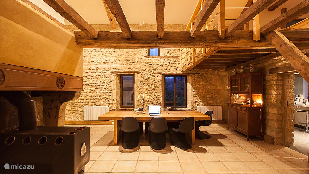 De ruime woonkamer van 80m2 heeft een dubbele schouw met een houthaard en open haard.
