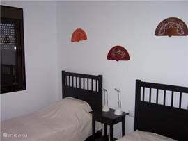 Slaapkamer 2: tweepersoons slaapkamer, met 2x 1-persoonsbed van 200 cm lang en goede matrassen, vaste kasten, rolluiken en openslaande ramen.